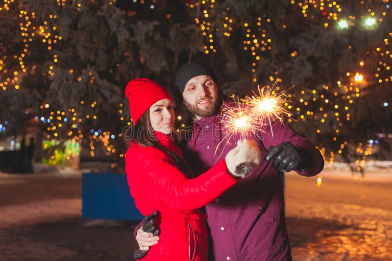 Outdoor portrait of young couple lighting sparkles stock photography