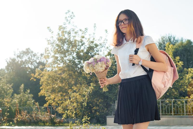 Outdoor portrait of young girl student in glasses with backpack and bouquet of flowers stock photos