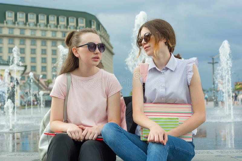 Outdoor portrait of young girls student with backpacks, books are sitting near the city fountain. Talking, learning. royalty free stock photos