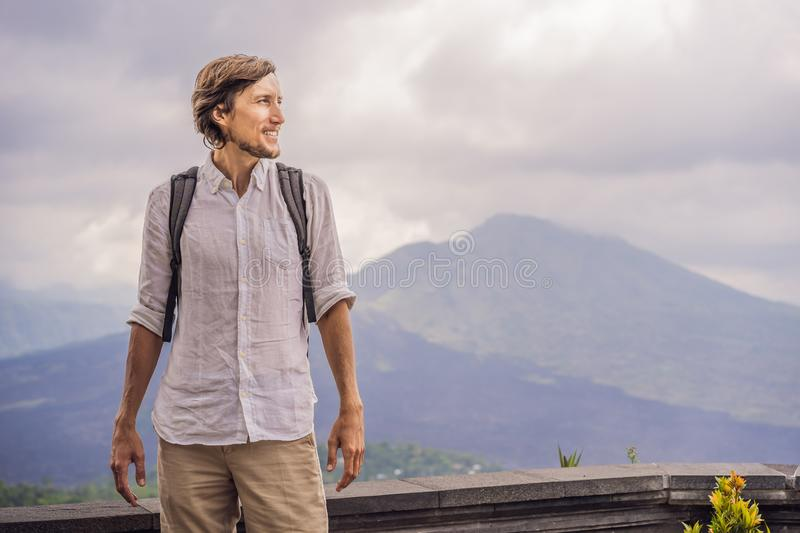Outdoor portrait of Young man looking on Batur volcano and Agung mountain view at morning from Kintamani, Bali royalty free stock images