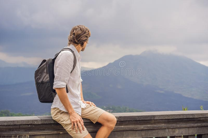 Outdoor portrait of Young man looking on Batur volcano and Agung mountain view at morning from Kintamani, Bali stock images