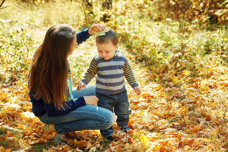 Outdoor portrait of a young mother with her baby. Mom and son in an autumn park. Outdoor portrait of a young mother with her baby. Mom and son in an autumn park stock photography