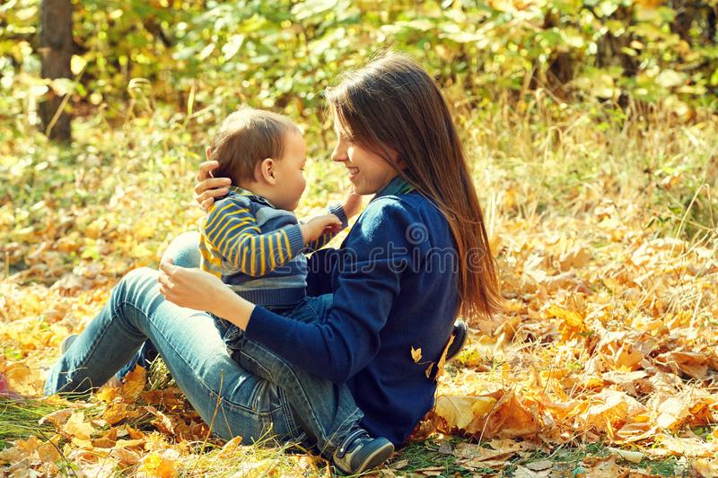Outdoor portrait of a young mother with her baby. Mom and son in an autumn park. Outdoor portrait of a young mother with her baby. Mom and son in an autumn park stock photo