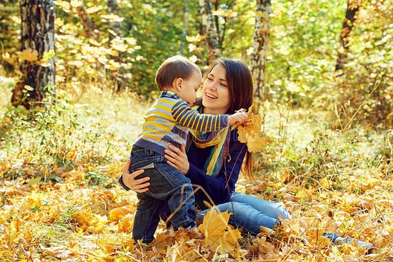 Outdoor portrait of a young mother with her baby. Mom and son in an autumn park. Outdoor portrait of a young mother with her baby. Mom and son in an autumn park stock photos