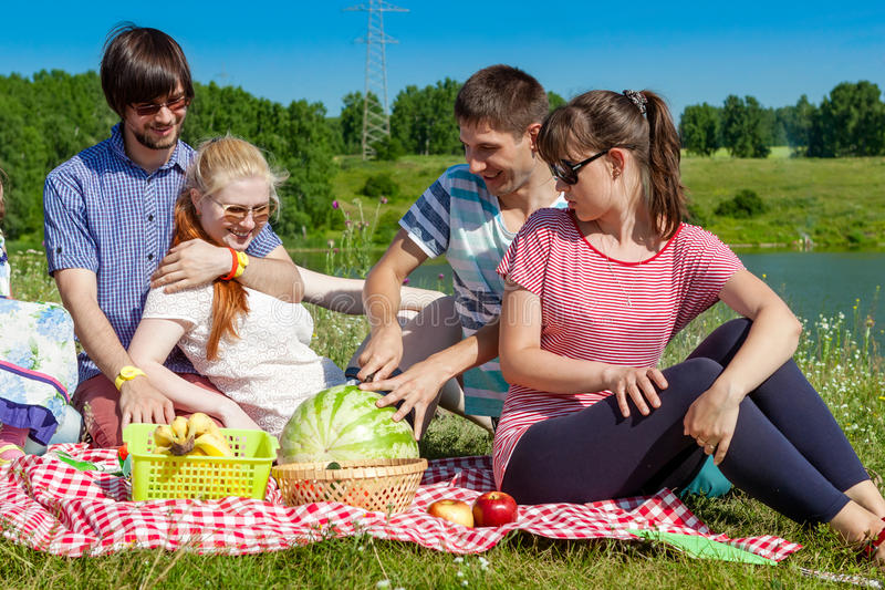 Outdoor portrait of young people having a picnic, eat watermelon stock images