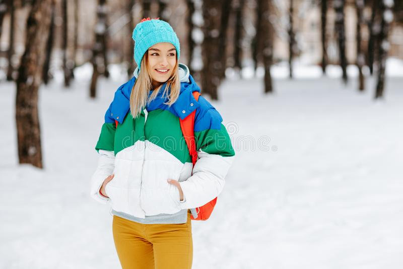 Outdoor portrait of young pretty happy smiling girl with bagpack posing in the park. Model wearing stylish warm clothes royalty free stock photos