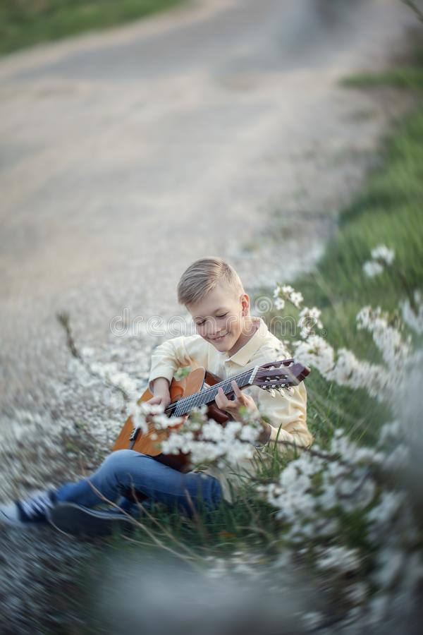 Outdoor portrait of a young teenager playing guitar and sitting on the road near park stock photography