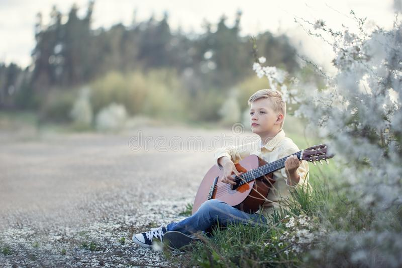 Outdoor portrait of a young teenager playing guitar and sitting on the road near park royalty free stock photos