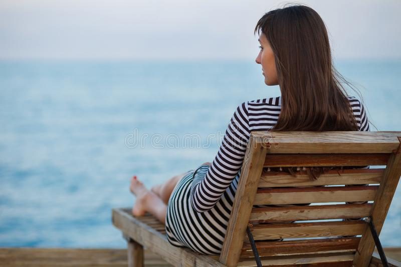 Outdoor portrit of beautiful young woman relaxing at the seacoast at the evening stock photo