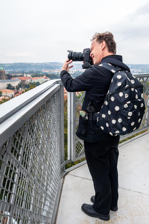 Caucasian male photographer in black suit and backpack at a tower with digital camera taking pictures of city view. stock images