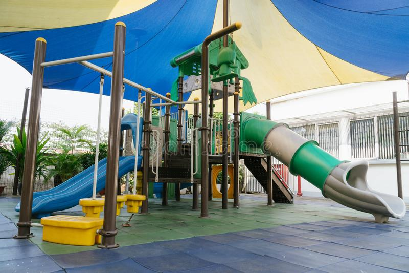 Outdoor public playground for kids in primary school under the shade royalty free stock photography