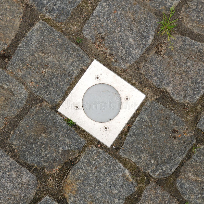 Outdoor Recessed Ground Lighting. An outdoor recessed ground lighting fixture on a paved sidewalk – square image stock photography