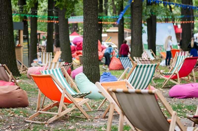 Outdoor Recreation Area with a many colorful soft chair bags, wooden tables and striped folding wooden chairs in a park. Sunny autumn day in the park stock images