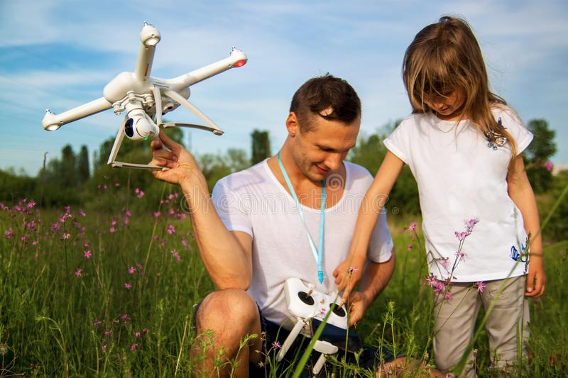 A man and little girl launch a radio-controlled aircraft or a drone or a helicopter into the sky. royalty free stock photo