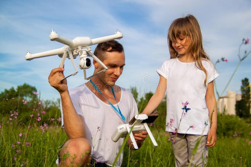 Young father shows his cute daughter how to control drone outdoors. stock image