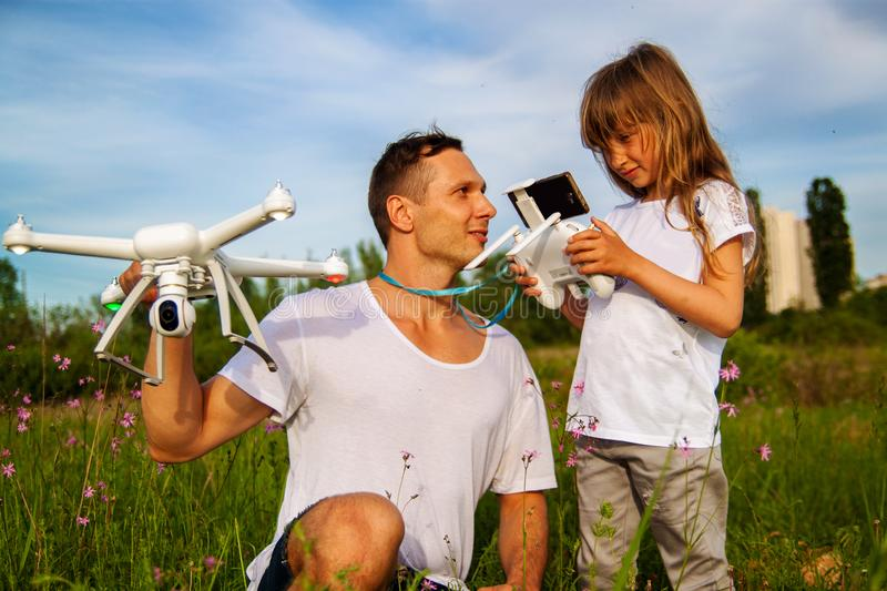 Young father shows his cute daughter how to control drone outdoors. royalty free stock images