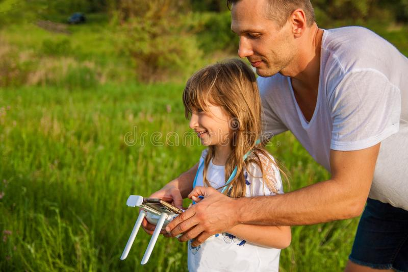 Young father shows his cute daughter how to control drone outdoors. stock photo