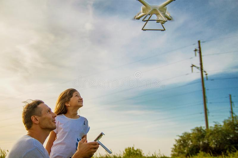 Young father shows his cute daughter how to control drone outdoors. royalty free stock photos