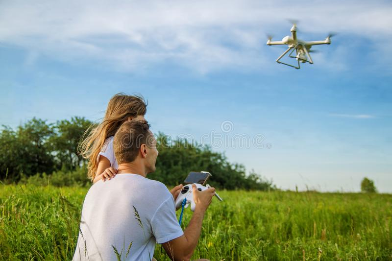 Young father shows his cute daughter how to control drone outdoors. royalty free stock photography