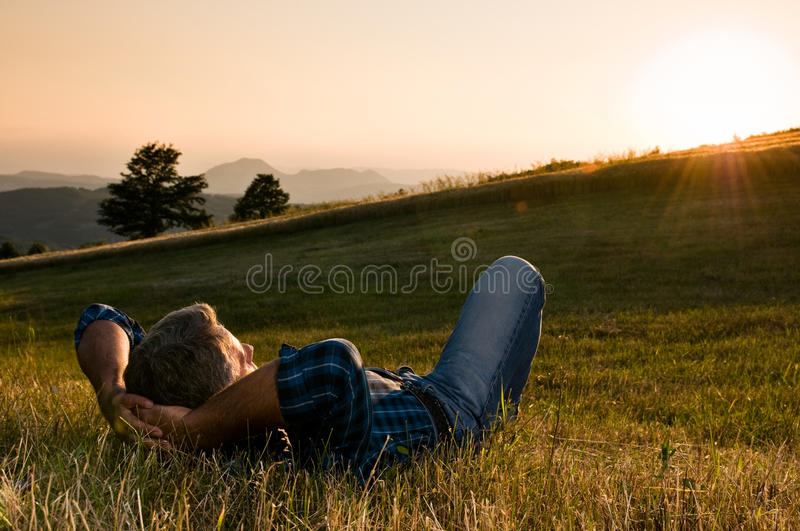 Outdoor relax. Mature man taking a break and relax in a meadow in the wonderful warm light of the sunset