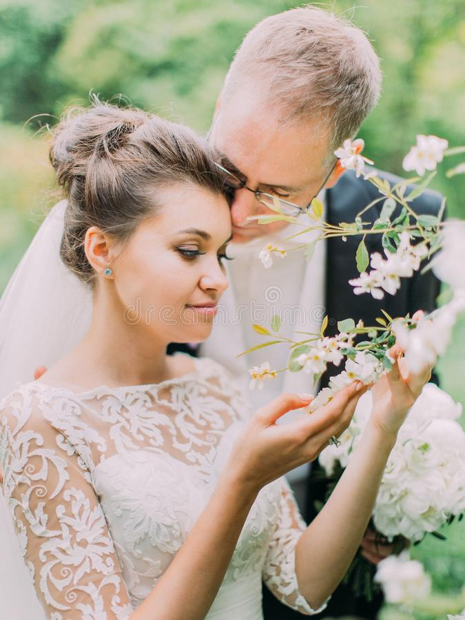 Outdoor romantic portrait of the hugging newlyweds enjoying the time in the garden. Outdoor romantic portrait of the hugging newlyweds enjoying the time in the stock photo