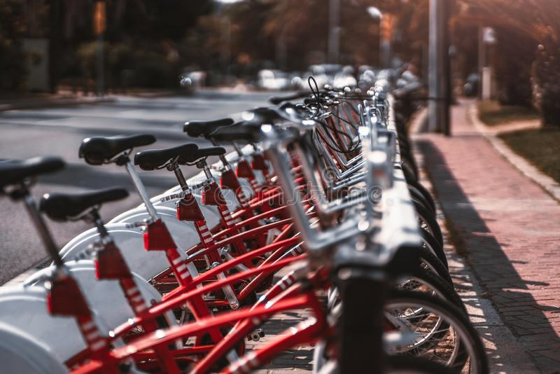 Outdoor row of red rental bikes. A long row of vivid red public bicycles outdoors with shallow depth of field; plenty of rentable city bikes on the street on a royalty free stock photography