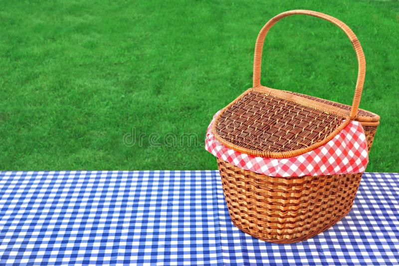 Outdoor Rustic Picnic Table With Hamper And Blue Tablecloth. Outdoor Rustic Picnic Table With Hamper And Blue Checkered Tablecloth On The Lawn In The Park Rest royalty free stock photo