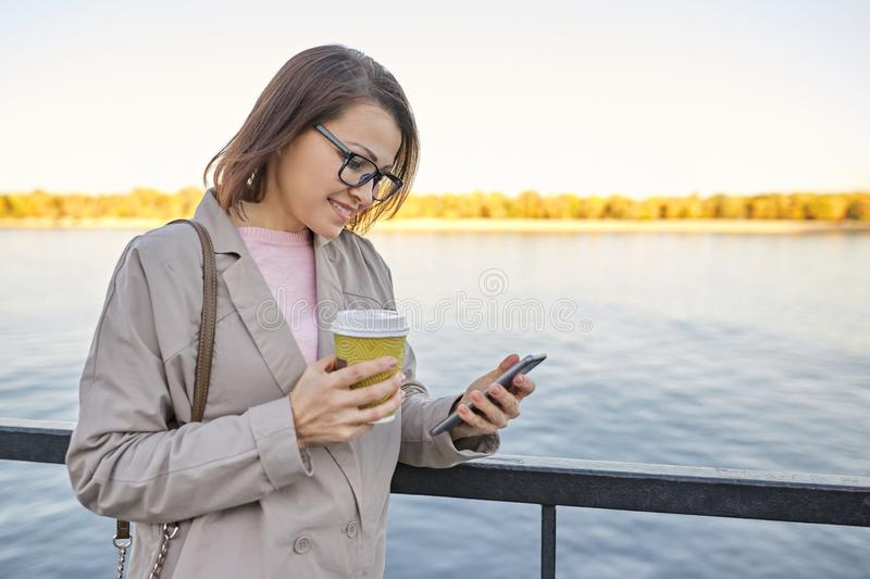Outdoor 40s woman portrait, smiling female with cup of coffee and smartphone stock image