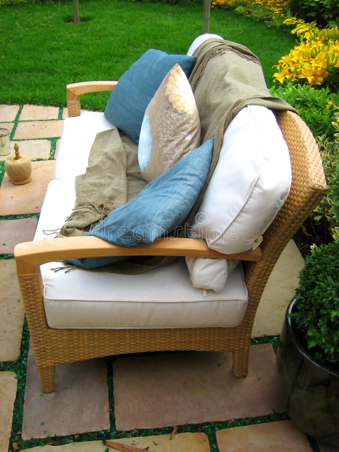 Outdoor seating. Relaxing cane seating with cushions and pillows in outdoor garden stock image