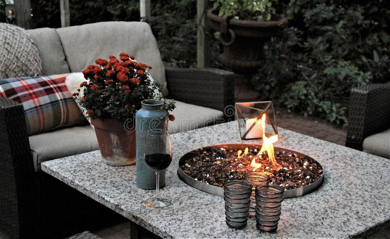 Outdoor seating arrangement around a gas fire pit table in the fall. Gas fire pit in the middle of a table with cosy autumn seating arrangement with plaid royalty free stock images