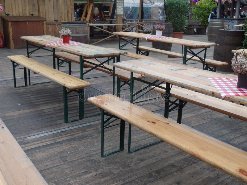 Outdoor seating for a Bavarian beer festival. Rows of wooden benches and tables set up to host a German beer festival stock photography