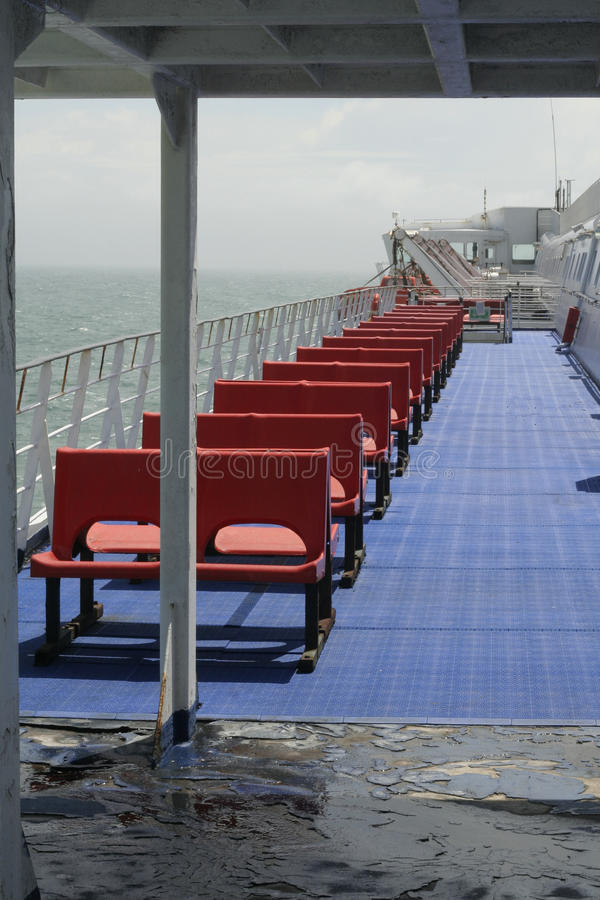 Outdoor seating on a ferry or ship. Empty red outdoor seating on a sailing ferry or passenger transport cruise ship royalty free stock image
