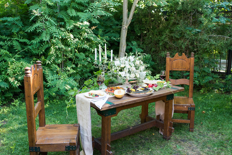 Outdoor served table with: a glass of red wine, melon, red currants, gooseberry, grilled vegetables. Wedding wooden banquet table. Wooden retro chair. Served stock photography