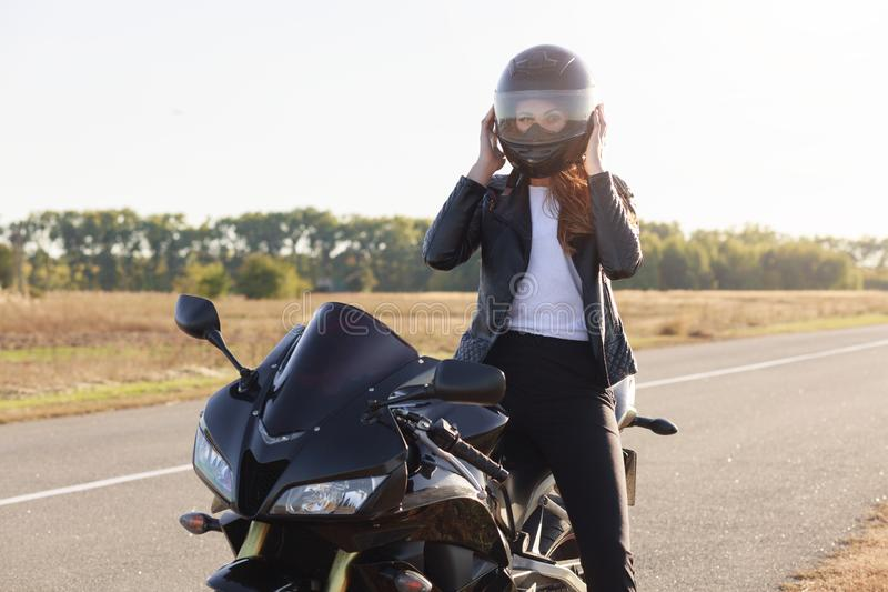 Outdoor shot of attractive confident moto driver with helmet wearing for safety, sitting on her motorbike at road, having stop, stock photos