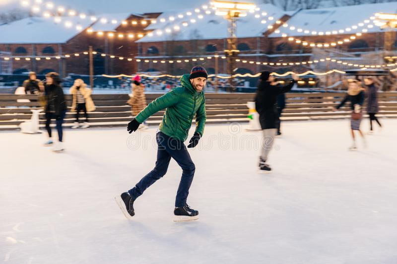 Outdoor shot of attractive man with beard, wears warm winter clothes, practices going skating on ice skate ring decorated with li stock photos