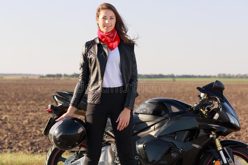Outdoor shot of attractive woman driver with dark hair stands near black fast motobike, holds helmet, wears leather jacket and red stock images
