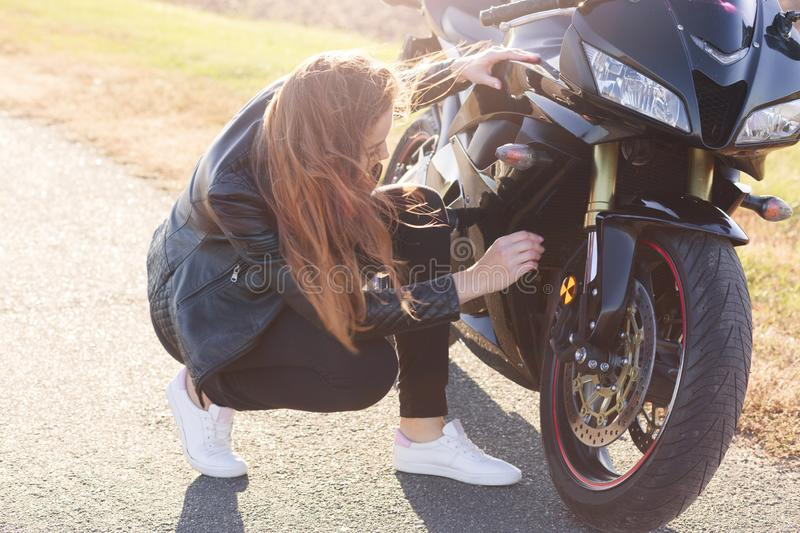 Outdoor shot of attractive woman with long dark hair squating near her modern motobike, wearing black clothes and white sneakers, stock photos
