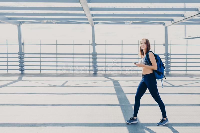Outdoor shot of beautiful woman wth slim body, dressed in casual top and leggings, carries bag, going in gym, uses modern smart ph. One for listening music, copy royalty free stock images
