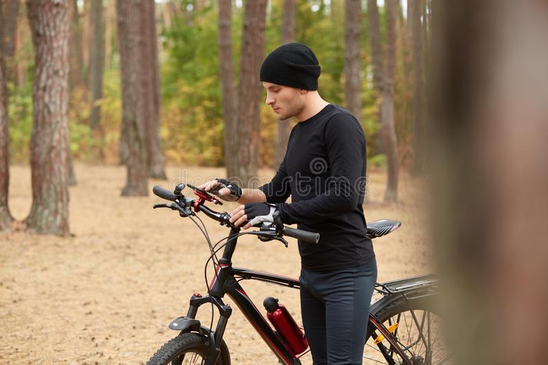 Outdoor shot of bicyclist on bike using navigator on smart phone, explore map and search GPS coordinates while biking inforest. Traveling, sports, active stock photos
