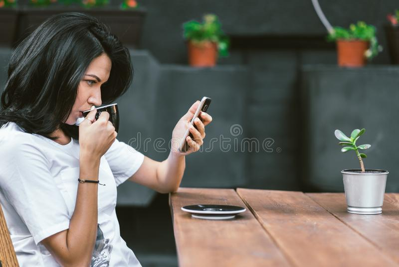 Outdoor shot of Caucasian girl in white t-shirt enjoying free wi-fi at coffee shop, surfing internet on mobile phone, reading royalty free stock photo