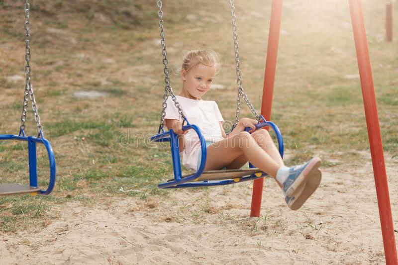 Outdoor shot of charming kid playing in park, little girl in kinderatren anf looks happy, expressing posive, cute child playing royalty free stock photography