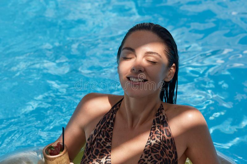 Outdoor shot of cheerful positive female posing with closed eyes, having sincere smile on face, lying near swimming pool, drinking royalty free stock image