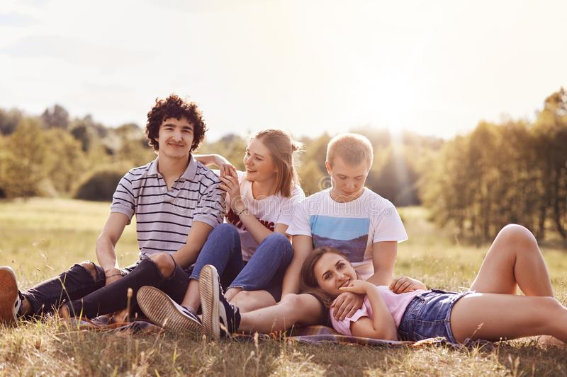 Outdoor shot of cheerful youth couples enjoy togetherness and spare time during summer day or weekend, sit closely to each other,. Admire beautiful nature, have stock images