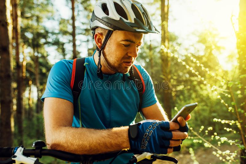 Outdoor shot of concentrated cyclist on bike using navigator on smart phone, explore map and search GPS coordinates while biking. In mountains. Travel, sports royalty free stock image