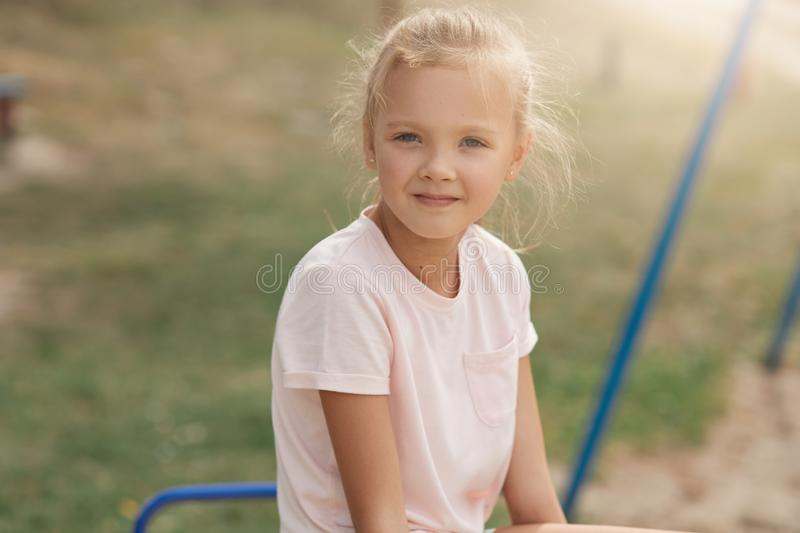 Outdoor shot of cute smiling little girl on swing, charming kid spending summer time outdoor, posing in open air, looking directly royalty free stock photography