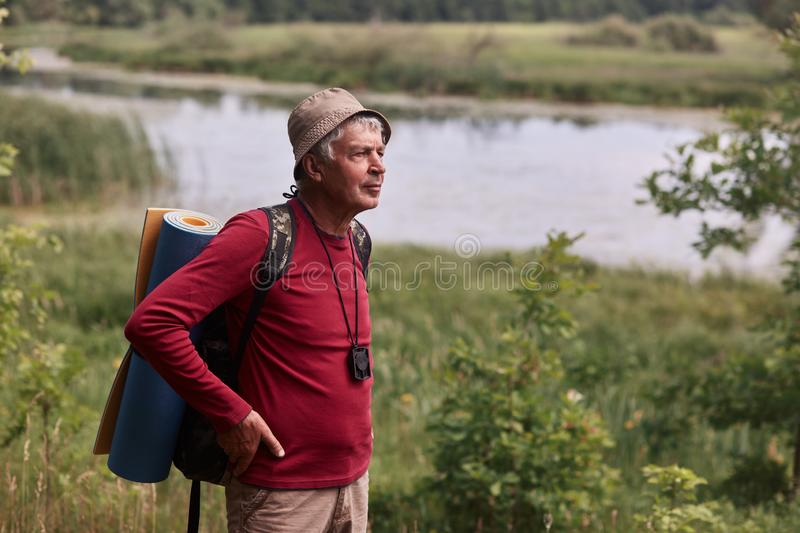 Outdoor shot of eldery man with backpack and rug, senior male poing in open air with hands on hips, decides where to go, wearing stock images