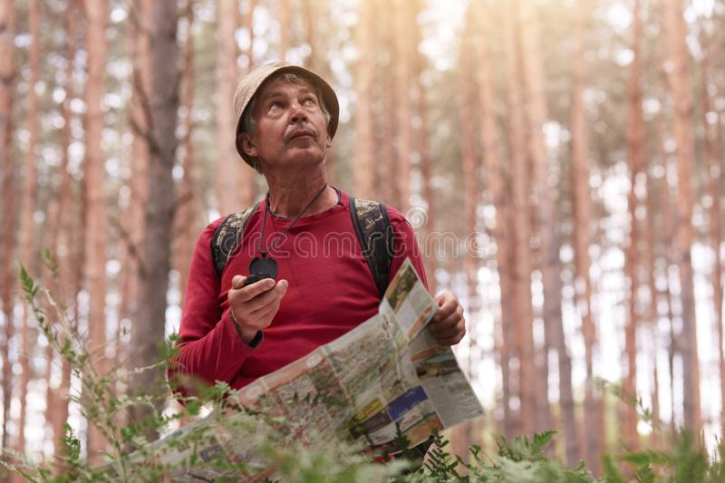 Outdoor shot of eldery man hiking and looking up at sky, holding compass and map in hands, try to find right way, having active royalty free stock photo