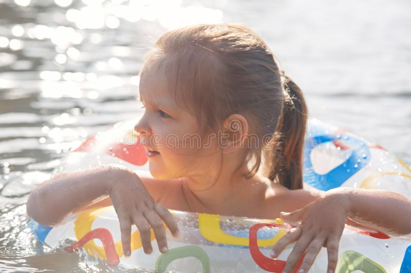 Outdoor shot of fair haired funny little girl spending free time in lake, learning to swim with swimming circle, looking aside, stock photos