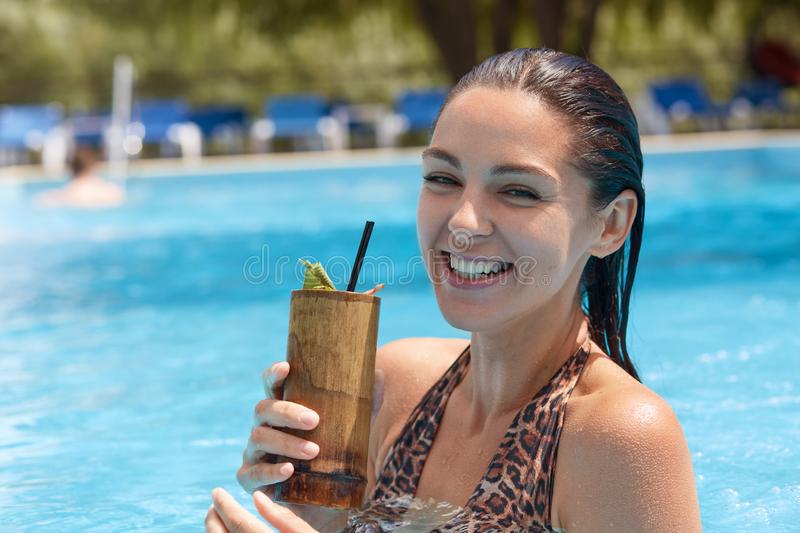 Outdoor shot of funny cheerful woman holding wooden glass with cocktail, looking directly at camera, laughing sincerely, wearing stock photo