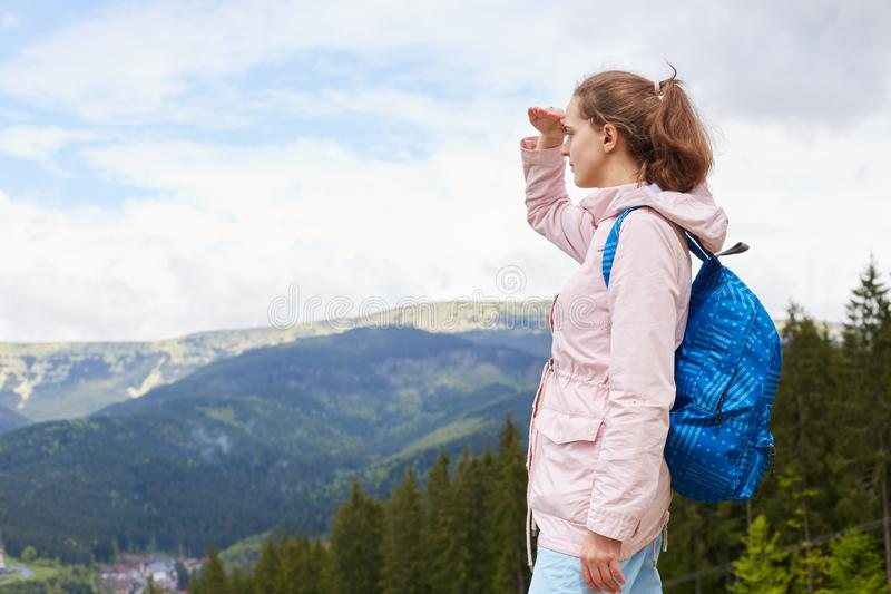 Outdoor shot of girl standing on top of hill, holding her hand near head, enjoing beautiful nature, having active rest in. Mountains, femalr wearing casual stock photography